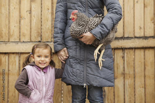 A woman in a grey coat holding a black and white chicken with a red coxcomb under one arm. A young girl beside her holding her other hand.