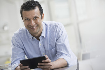 A man in a blue shirt leaning on a desk, holding a digital tablet.