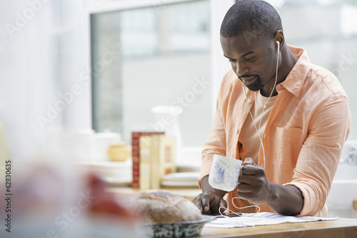 An office or apartment interior in New York City. A man in an orange shirt at the breakfast bar, having a cup of tea.