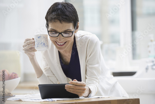 An office or apartment interior in New York City. A woman dressed for work in cream jacket, holding a cup of coffee. Checking her digital tablet.