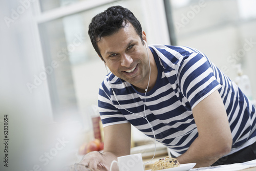 An office or apartment interior in New York City. A man in a striped tee shirt leaning on the breakfast bar.