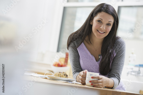 An office or apartment interior in New York City. A young woman with long black hair, having a cup of coffee.