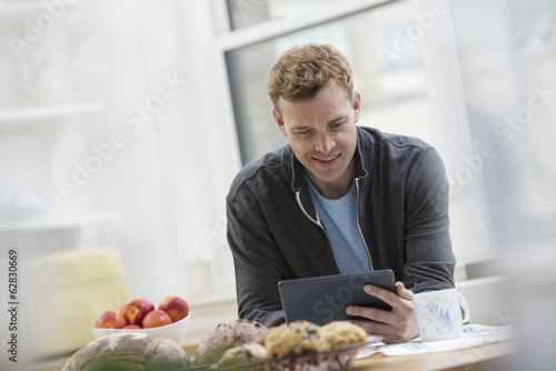 An office or apartment interior in New York City. A man in a sweatshirt top using a digital pad. Leaning on a breakfast bar.