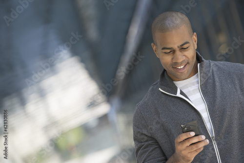 Business people in the city. Keeping in touch on the move. A man in a grey zipped sweatshirt using his smart phone