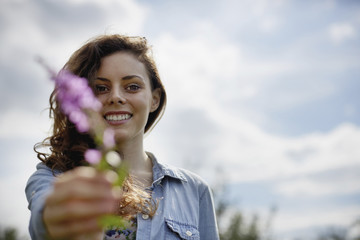 A young woman holding out a wild flower with pink petals.