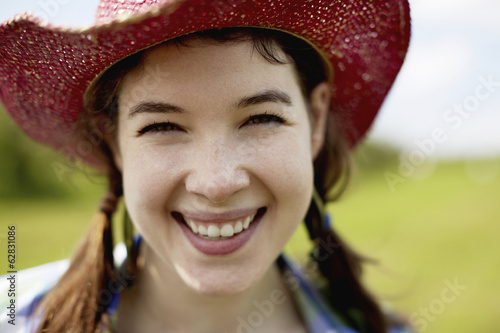 A young woman in a pink straw hat smiling broadly.