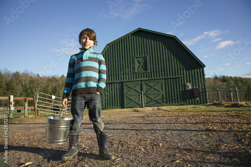 A young boy in an animal paddock, holding a bucket of feed. Animal sanctuary.