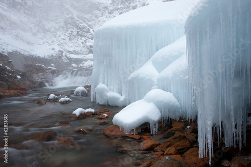 Honshu island, Nagano, Japan. Icicles and blocks of frozen snow by a stream.