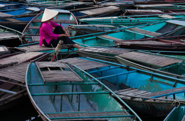 Lost in thought, a woman sits amidst a raft of boats. Ninh Binh, Vietnam