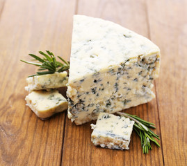 Tasty blue cheese with rosemary, on wooden table