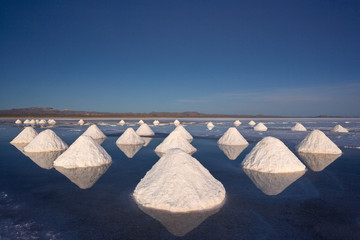 Piles of salt dry in the arid atmosphere of Bolivia's Salar de Uyuni.
