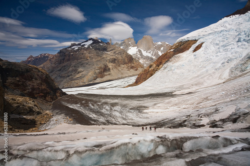 Several hikers on a glacier and Fitz Roy loom in the background. Los Glaciares National Park, Argentina