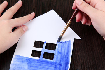 Female hand coloring paper cabin, on wooden background