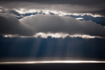 Sun rays stream down thru clouds, Kamai National Park, Alaska, USA