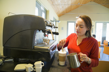 A young woman making coffee using a large coffee machine. Pouring frothed milk onto a cup.