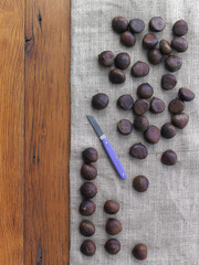 Chestnuts being prepared for roasting. Tabletop, hessian fabric and knife.