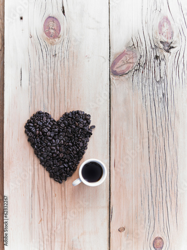Overhead view of a heap of roasted organic coffee beans in a heart shape, arranged on a tabletop. A cup of black coffee.