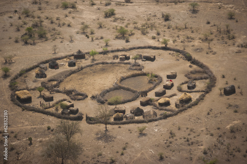 An aerial view of a small rural village settlement, with traditional buildings and animal enclosures.