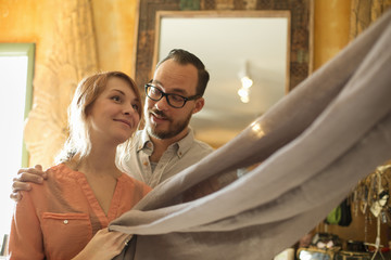 Two people, a couple running an antique store. Small business. Holding a piece of linen fabric.