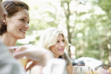 Two woman sitting at a table side by side in a garden. Talking and laughing.