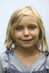 A young girl with blonde hair, and blue eyes. Smiling and looking at the camera.