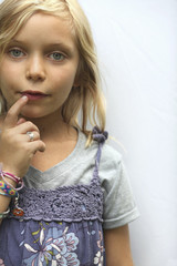 A young girl with blonde hair, and blue eyes.  Her hand to her mouth.