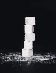Stack of sugar cubes, balancing one on top the other, on black backdrop