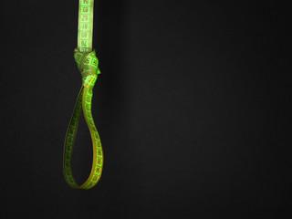 Tape measure noose on dark background - diet concept