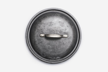 Cookware, a black round pot lid, a well used dented piece of cookware.