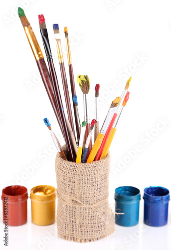 Brushes with paints in vase isolated on white