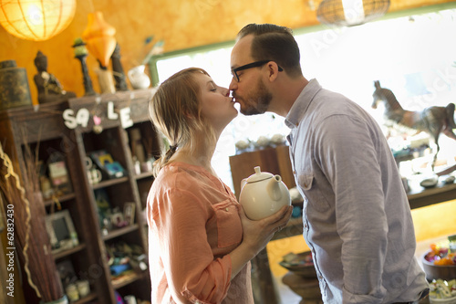 Two people, a couple running an antique store. Small business. Kissing each other.
