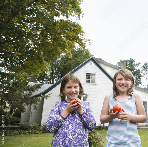 Two children, girls standing in a garden holding and eating fresh picked tomatoes.