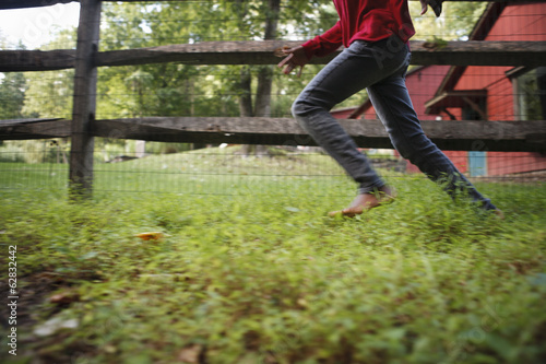 A boy running around a paddock fence outdoors.