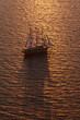 A three-masted sailing ship with full sail on the Aegean Sea at sunset.