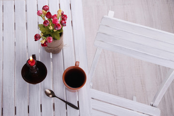 Composition with cup of hot drink, candle and flowers