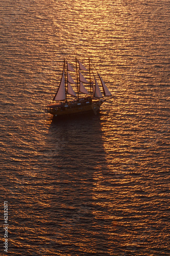 A three-masted sailing ship with full sail on the Aegean Sea at sunset.