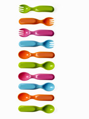 Colourful plastic spoons and forks, for use by infants and babies.