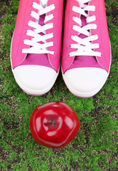 Beautiful gumshoes and apple on green grass background