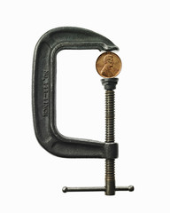 A coin in a clamp. Feeling the pinch, economic squeeze.