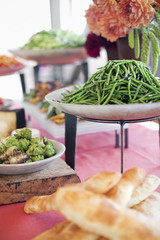 Organic prepared salads, vegetables and fruit on dishes, laid out for a party. A laden table. Flowers in a vase.  A farm stand food stall.