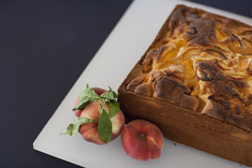 A square baked peach cake on a board with fresh peaches. Fruits. Organic fresh food on a farm stand with a herb garnish.