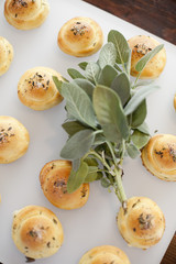 Organic dinner bread rolls on a white board with salt and sage garnish