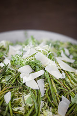 Organic prepared vegetable dish for a party. Farmstand. Grilled Asparagus and Frise Salad. Parmesan cheese shavings.