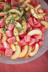 Organic prepared farm stand party food. Summer fruit salad of watermelon, peaches and mint.