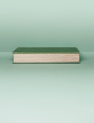 A hard cover book with a green cover, and white paper page edges, lying horizontal on a pale green background.