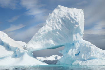 Icebergs floating on the Antarctic southern oceans. Eroded by wind and weather, creating natural ice arches.