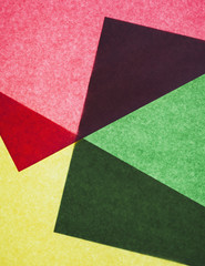 Pieces of colourful, recycled construction paper, overlapping and laid out at random.