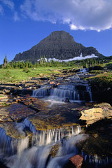 The landscape of Glacier National Park, to Mount Reynolds peak, and Logan Pass. Water flowing over rocks.