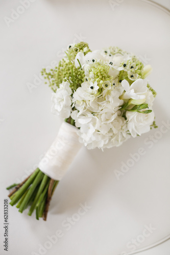 A wedding bouquet. White cut flowers, green seed heads, and foliage. Green stems and white ribbon.