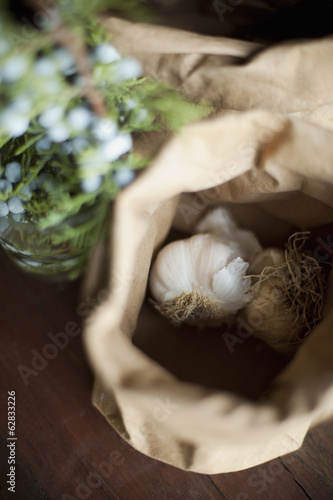 Organic ingredients on a table. Garlic bulbs in a brown paper bag. A herb with  blue flowers. Fresh ingredients.